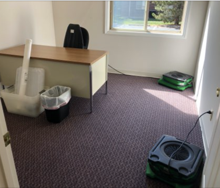 Office space with a desk and green drying equipment.